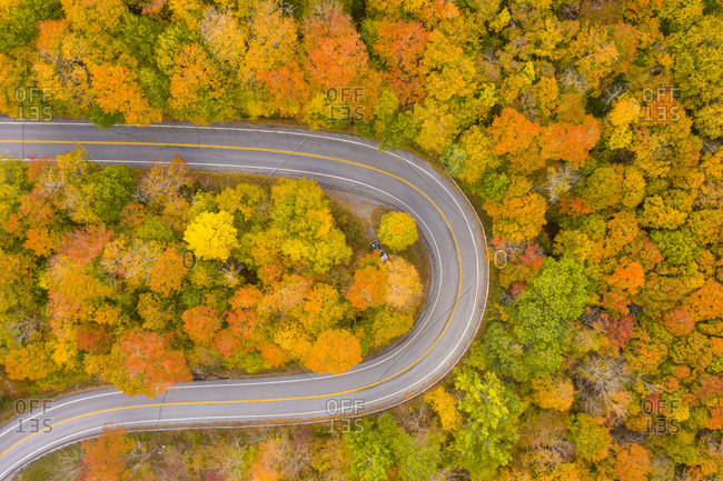 Winding road leading through fall foliage in New Haven, Vermont viewed from above