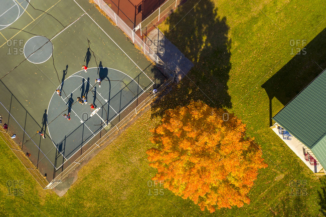 Drone shot over basketball court and colorful trees in fall, Middlebury, Vermont