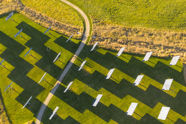 Bird's eye view over winding road surrounded by solar panels in a field in Middlebury, Vermont