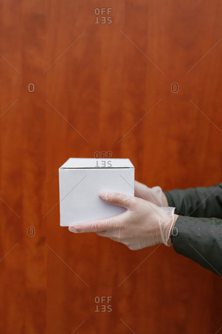 Hands in protective gloves hold the box against a uniform background in Penza, Russia