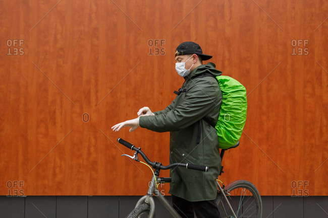 A courier wearing a protective mask puts on protective gloves in Penza, Russia