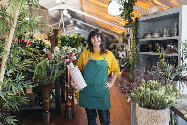 Stock photo of beautiful and happy woman working in florist shop.