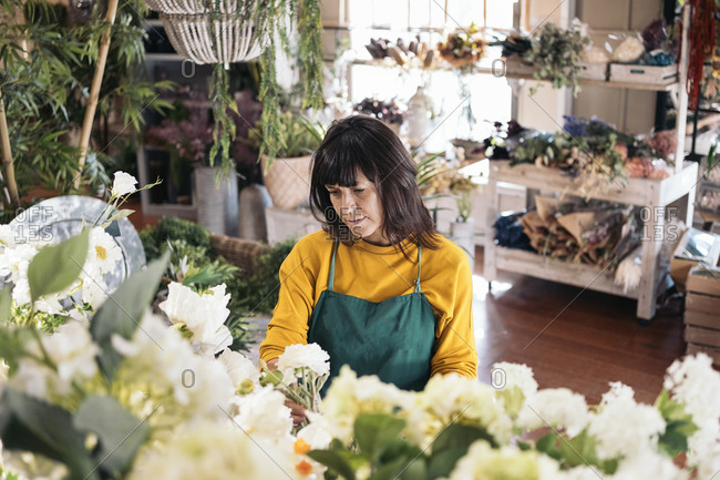 Stock photo of woman working in florist shop taking care of white flowers.