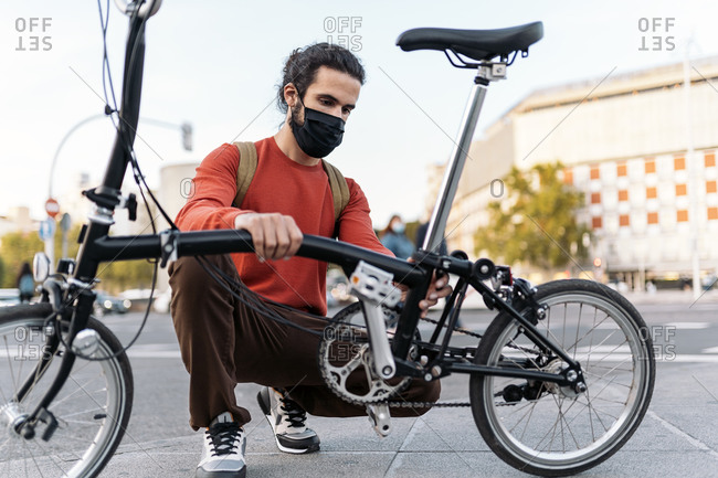 Stock photo of man wearing face mask folding his bike in the street.