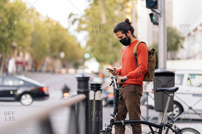 Stock photo of man wearing face mask due to covid19 using his phone in the street and holding a bike.
