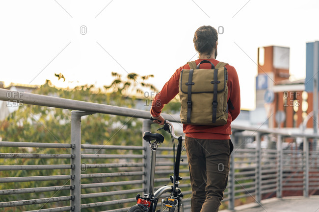 Stock photo of faceless man carrying his detachable bike and walking in the street.