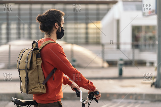 Stock photo of man wearing face mask waiting in a zebra crossing with his detachable bike.