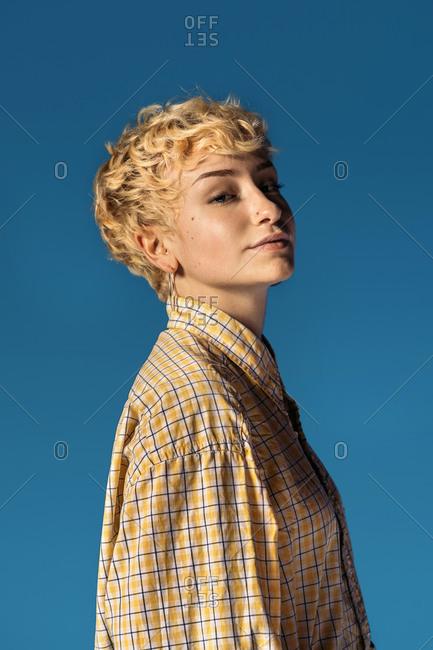 Stock photo of expressive girl wearing yellow shirt looking at camera and smiling.