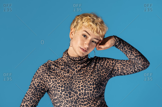 Stock photo of expressive girl wearing animal print shirt looking at camera and smiling.