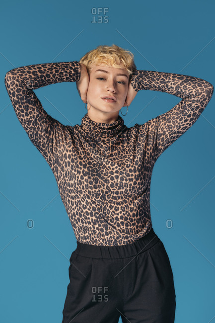 Stock photo of expressive girl wearing animal print shirt looking at camera and touching her head.