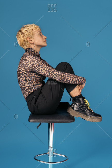 Stock photo of expressive girl wearing animal print shirt sitting in a chair with her eyes closed.
