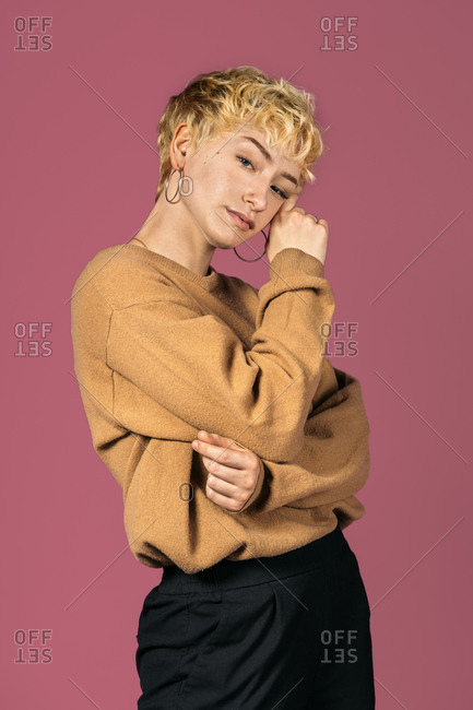 Stock photo of expressive girl looking at camera and touching her face over pink background.
