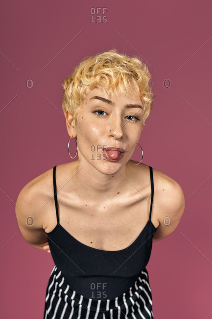 Stock photo of funny girl with her tongue out looking at camera over pink background.