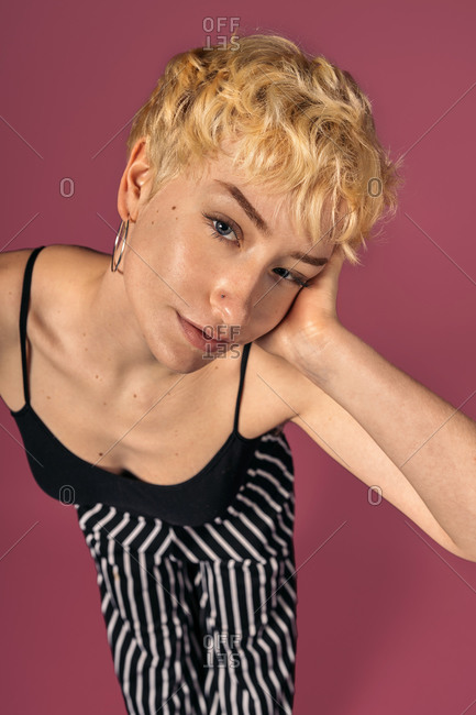 Stock photo of expressive girl wearing black tank top standing and looking at camera over pink background.