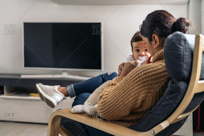Stock photo of young mother sharing cute moment with her little baby in the living room.