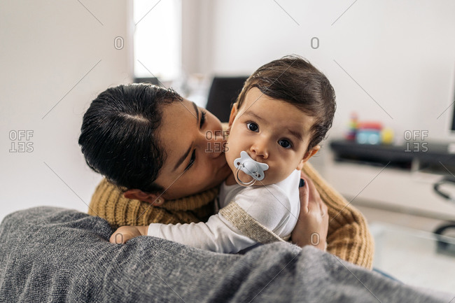 Stock photo of young mother kissing her little baby in the sofa.