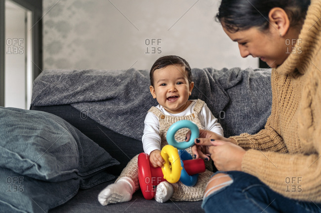 Stock photo of young mother playing with her little baby in the living room.