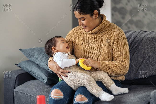Stock photo of smiley woman holding her little baby while sitting in the sofa.