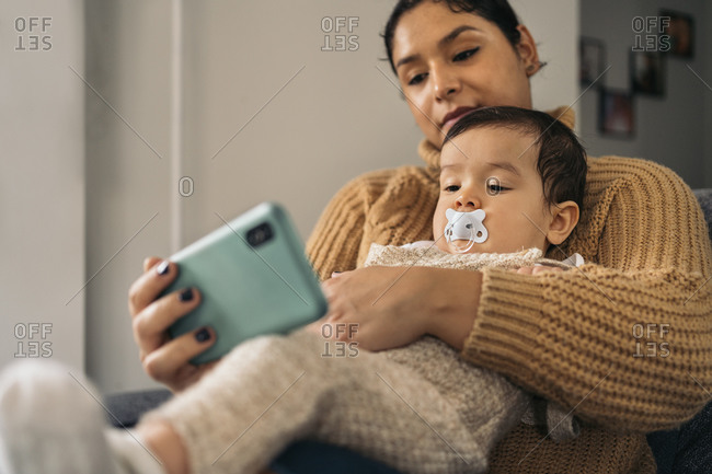 Stock photo of happy mother and her baby watching cartoons in the phone at home.