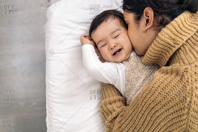 Stock photo of young mother kissing her little baby and sharing cute moment.