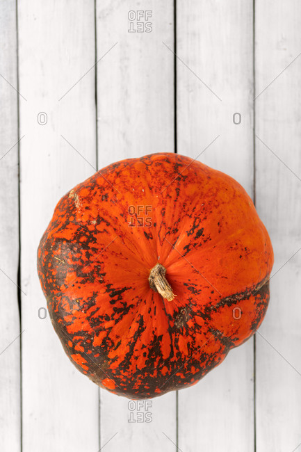 Whole hokkaido pumpkin on white wooden background top view