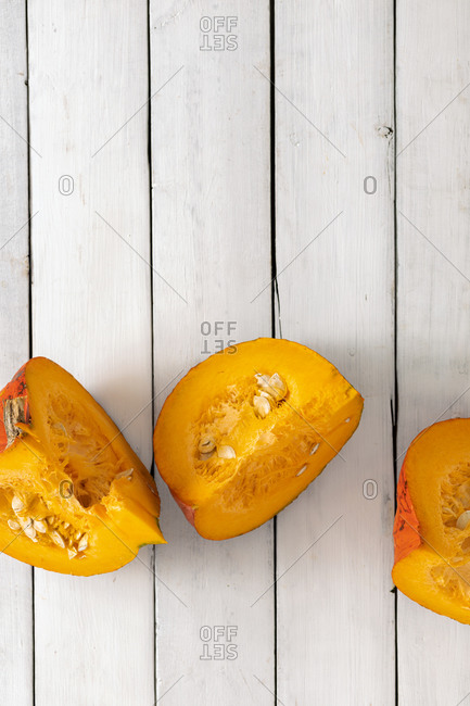 Three pieces of hokkaido pumpkin on white wooden background top view