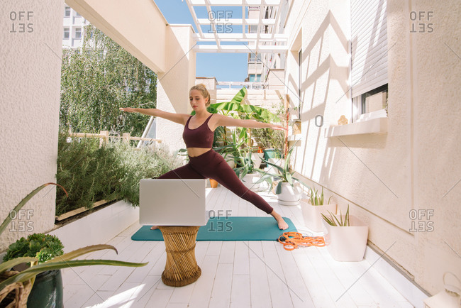 Beautiful woman doing yoga by watching online course