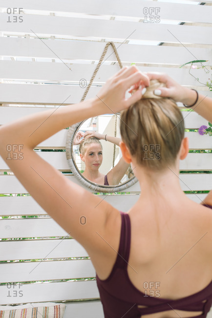Blonde woman throwing her hair up in a bun before working out at her home