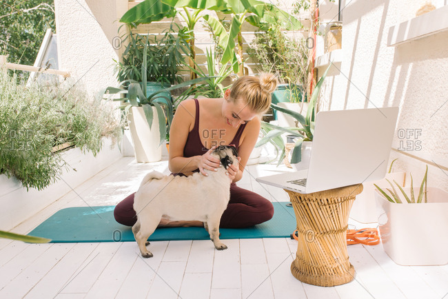 Blonde woman petting her pug dog while working out at her home