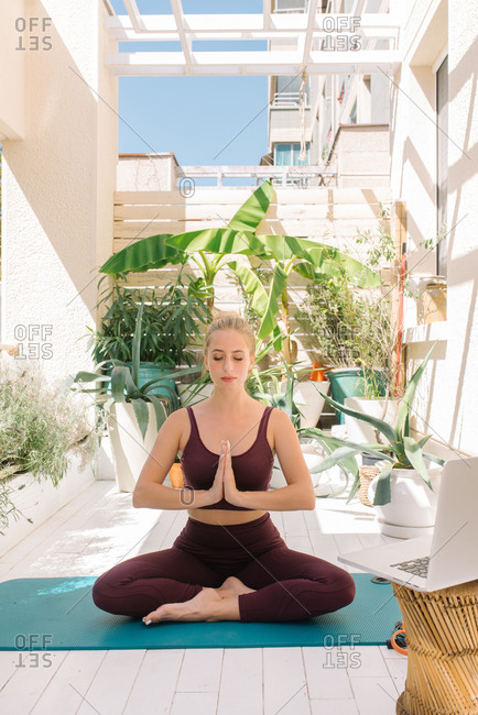Blonde woman meditating on her home balcony