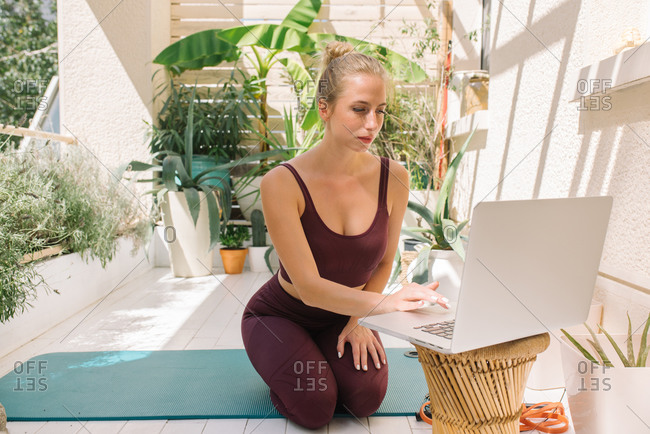 Beautiful blonde woman setting up her laptop for an online yoga class
