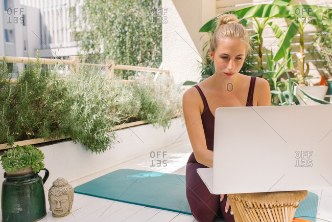 Woman setting up her laptop on her Bohemian style balcony for an online yoga class