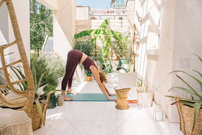 Blonde woman in downward dog position while working out at home on her balcony