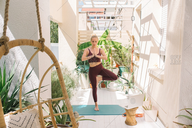 Woman practicing the tree yoga pose on her balcony