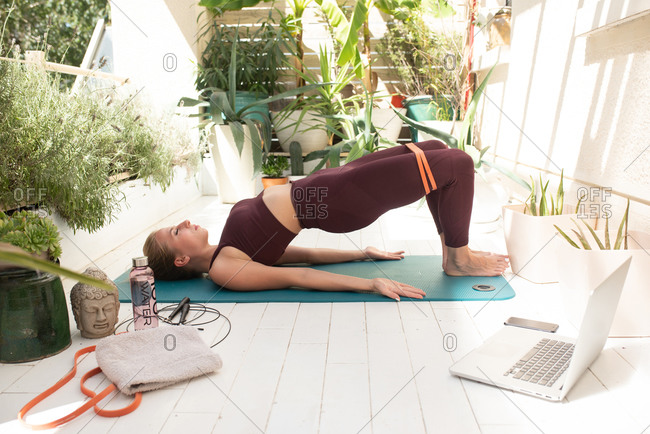 Blonde woman practicing the bridge pose while doing online yoga class