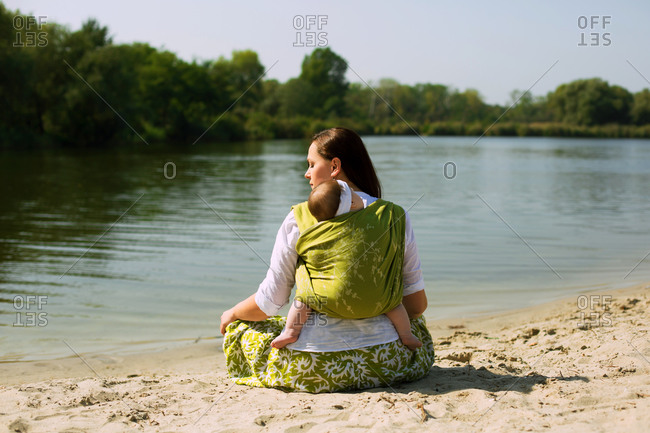 Beautiful mom sit in lotus pose at river bank with wrapped baby back