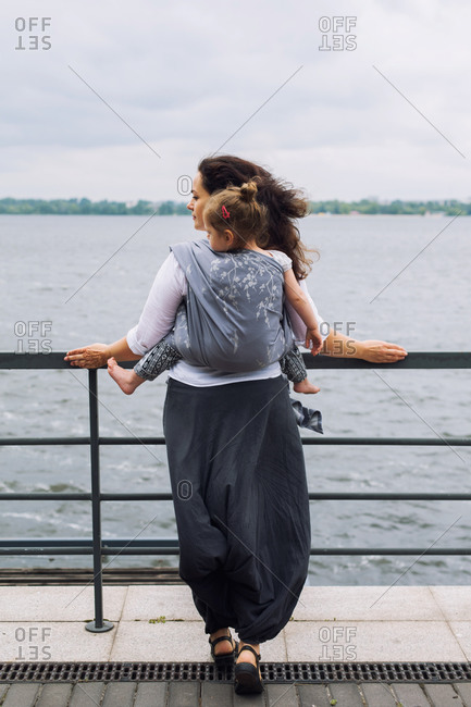 Mother stay back with wrapped in sling daughter, baby wearing