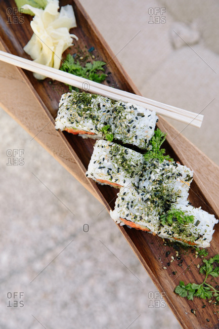 Close up of sushi served on a wooden tray with chopsticks