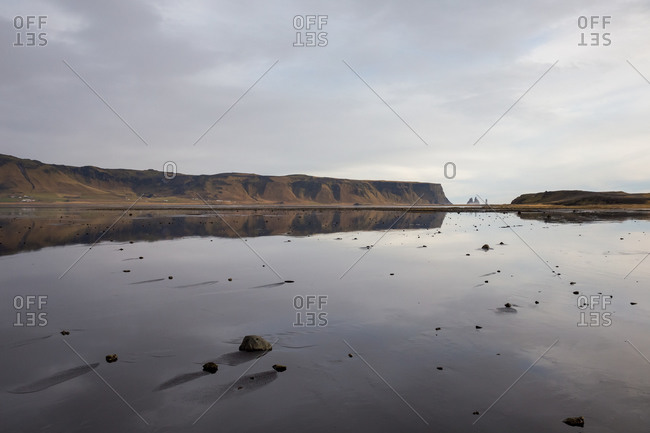 Reflections in shallow tidal water at reynisfjara, iceland