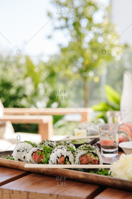 Sushi served on a wooden table with chopsticks outdoors