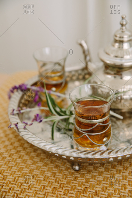 Tea served in glasses on a silver tray with a fancy teapot