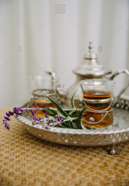 Tea served in fancy glasses on a silver tray with teapot