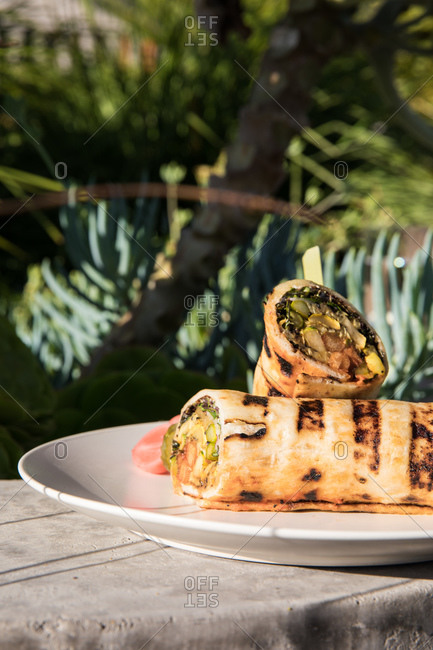 A grilled wrap on an outdoor table