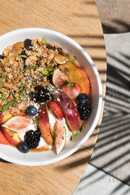 Overhead view of a granola and fruit bowl on an outdoor table