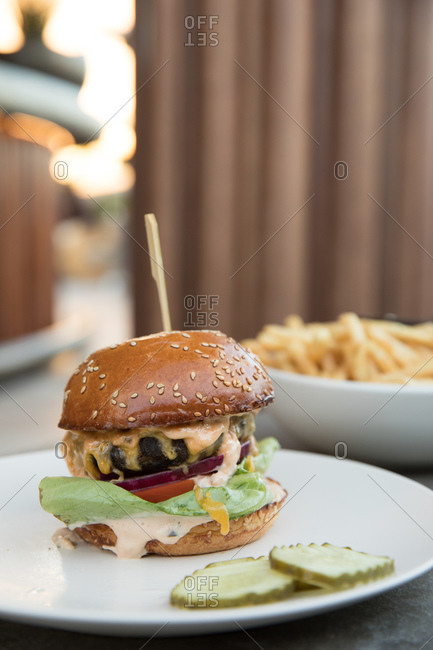 Cheeseburger served on a plate beside a bowl full of fries