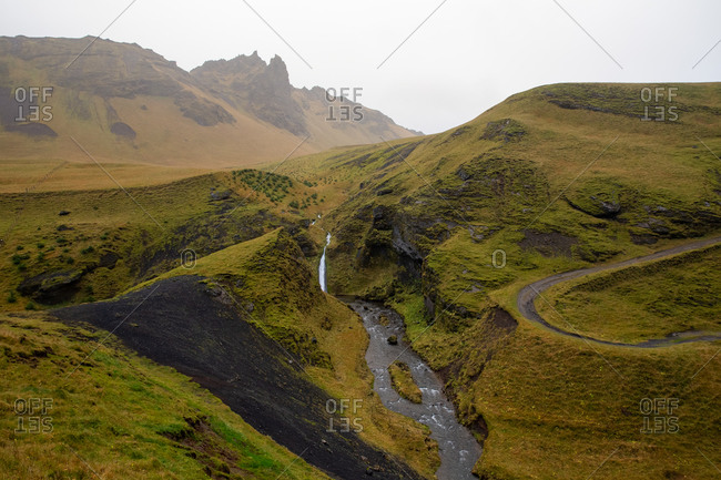 Stream cuts through the green mossy hills in iceland