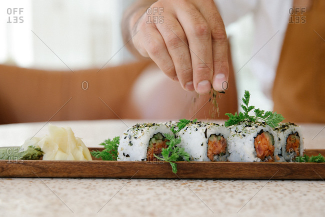 Chef preparing sushi on a wooden tray
