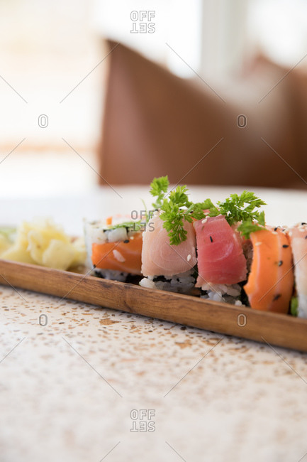 Close up of rainbow sushi served on a wooden tray