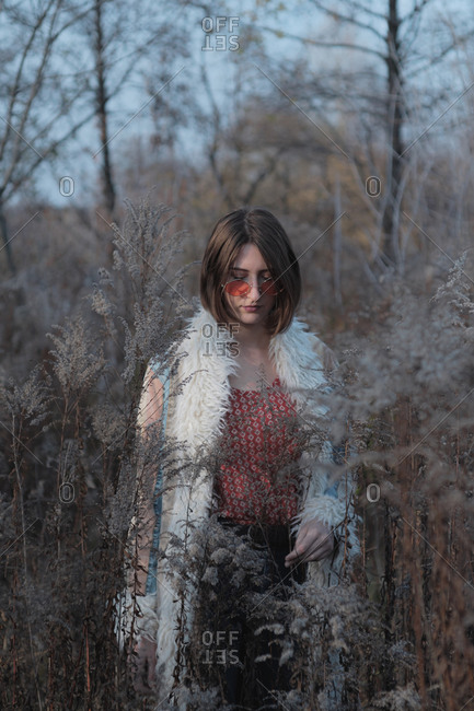 Young woman in hippie coat and red sunglasses among weeds and gr