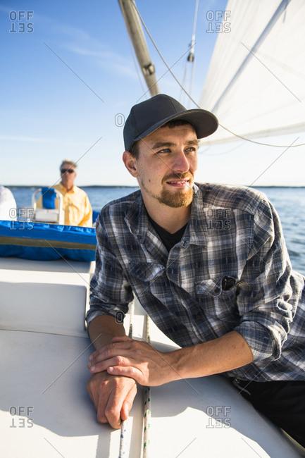 Young man enjoying summer sail during golden hour